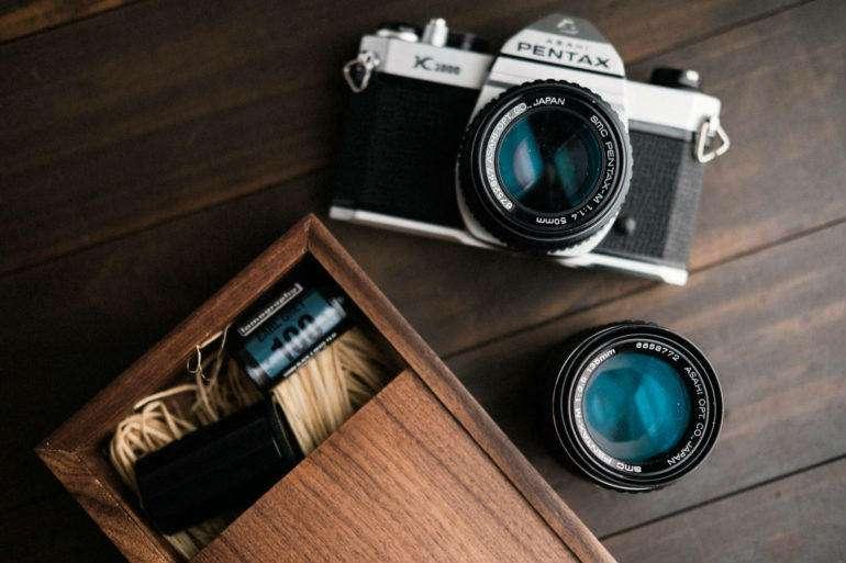 دوربین دوستداشتنی Pentax K1000 و یک حلقه فیلم 135 با حساسیت 100 در کنار آن