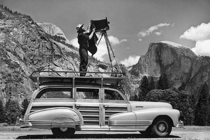 انسل آدامز، شخصیت تاثیرگذار و شهیر تاریخ عکاسی، دوربین را روی سقف خودرویی که به سکوی متحرک او تبدیل شده است، تنظیم میکند.